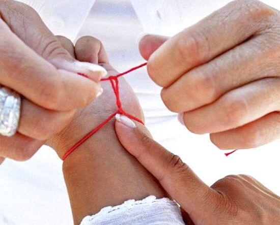 Мне завязывают красную нитку от сглаза