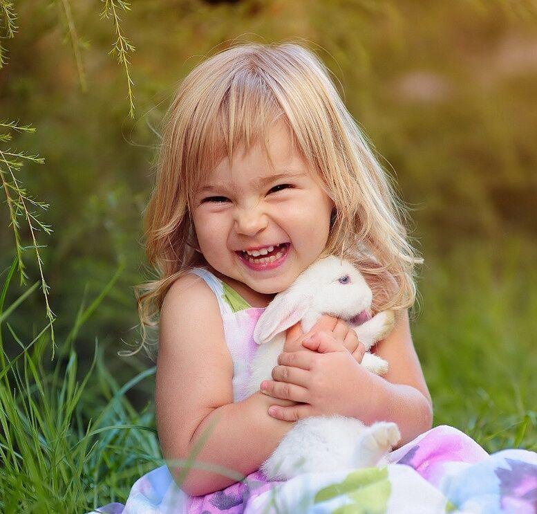 Счастливая девочка держит кролика